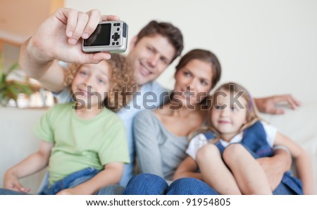 Happy family taking a photo of themselves in their living room - stock photo