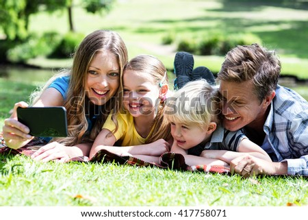 Happy family taking a selfie from mobile phone in the park - stock photo