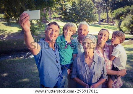 Happy family taking a selfie in the park on a sunny day - stock photo