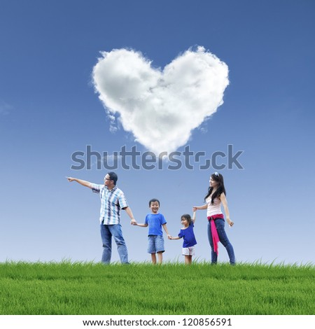 Happy family taking a stroll in the park under love shaped cloud - stock photo