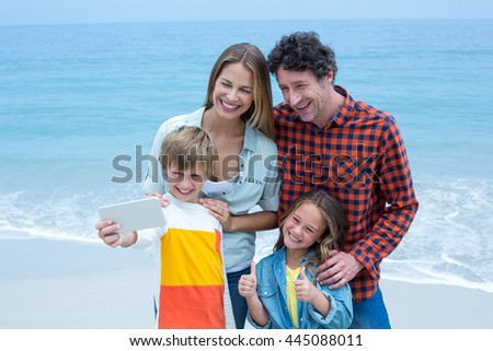 Happy family taking selfie while standing at sea shore - stock photo