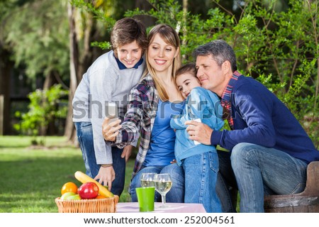 Happy family taking selfportrait through smartphone at campsite - stock photo
