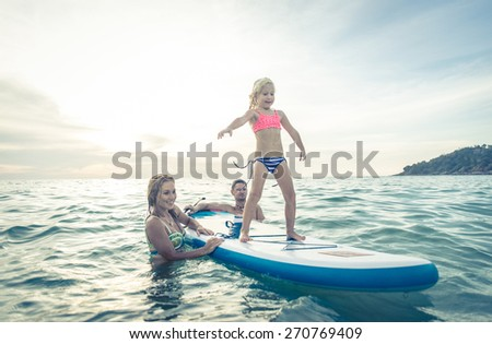 happy family teaching the daughter to stand on the surf in the ocean. concept about family, sport, active people - stock photo