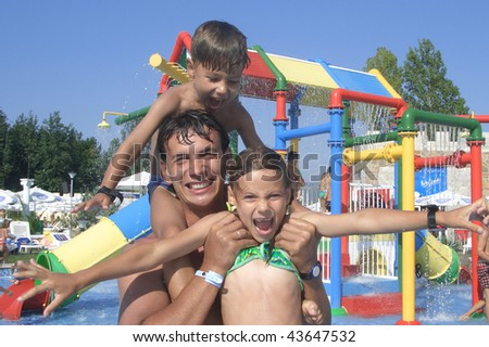 Happy family that enjoy spending time together in the water park - stock photo