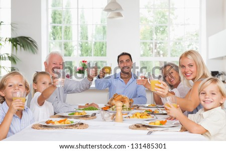 Happy family toasting around the table at thanksgiving dinner - stock photo