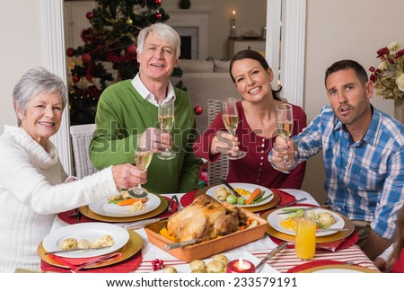 Happy family toasting at camera during christmas dinner at home in the living room - stock photo