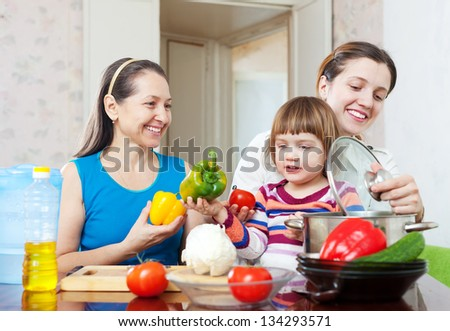 Happy family together cooking vegetarian lunch with vegetables at home - stock photo