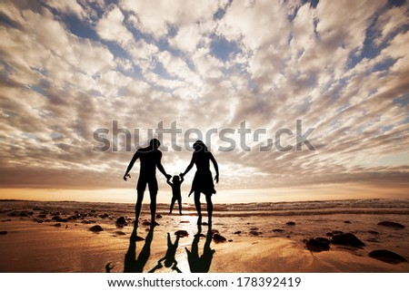 Happy family together hand in hand on the beach at sunset, summer time. Mother, father and a little child - stock photo