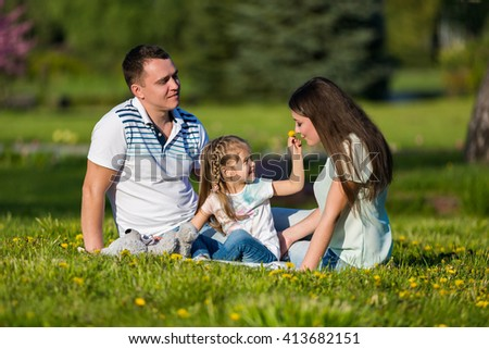 Happy family together in the park, smelling flowers. Allergy concept - stock photo