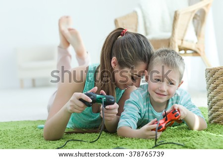 Happy family together. Mother and baby son, playing video games. Family rest. - stock photo