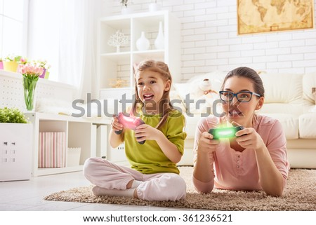 happy family together. mother and her child girl playing video games. family relax. - stock photo