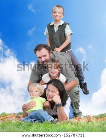 Happy family together on the grass against blue sky.