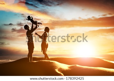 Happy family together, parents celebrating their little child by the seaside at sunset, summer time. Birth, mother, father concepts  - stock photo