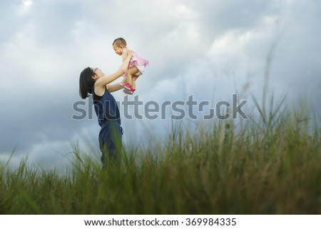 Happy family together, parents with their baby at sunset. Mother raising baby up in the air - Vibrant color effect