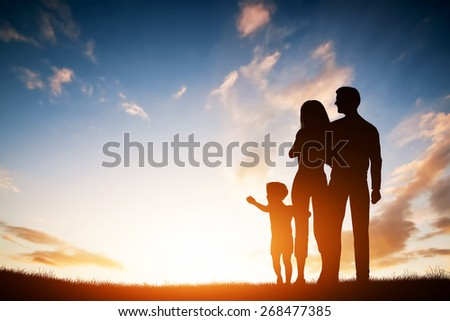 Happy family together, parents with their little child at sunset. Boy reaching the sun - stock photo