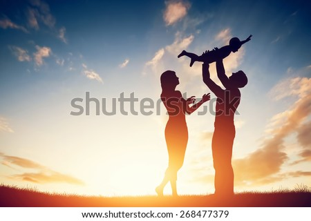 Happy family together, parents with their little child at sunset. Father raising baby up in the air. - stock photo