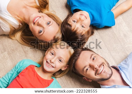 Happy family. Top view of happy family of four bonding to each other heads and smiling while lying on the hardwood floor  - stock photo