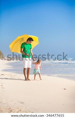 Happy family under yellow umbrella on white sandy beach - stock photo