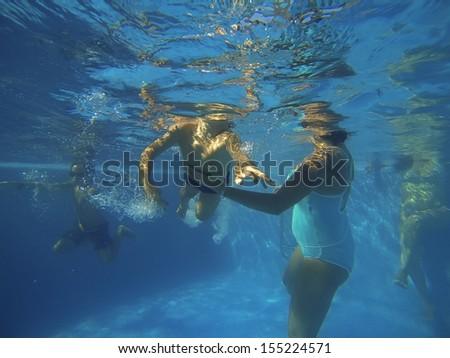 Happy family underwater in swimming pool. - stock photo