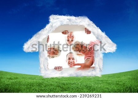 Happy family unpacking boxes against green field under blue sky - stock photo