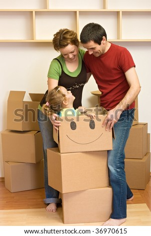 Happy family unpacking in their new home with lots of cardboard boxes