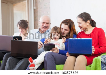 Happy family uses electronic devices in home interior