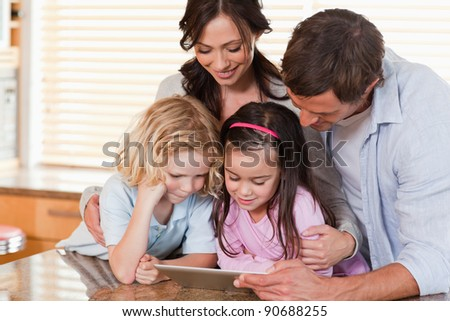 Happy family using a tablet computer together in a kitchen - stock photo