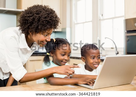 Happy family using laptop in the kitchen at home - stock photo