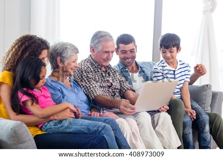Happy family using laptop on sofa at home - stock photo