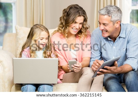 Happy family using laptop, tablet and smartphone at home