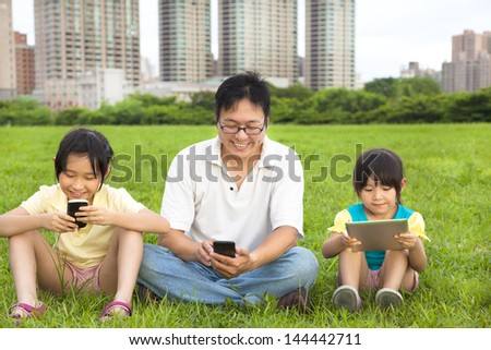 happy family using smart phone and tablet pc outdoor - stock photo