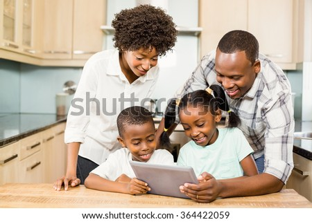 Happy family using tablet in kitchen at home