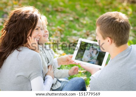 Happy family using tablet PC outdoors in autumn park - stock photo