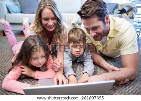 Happy family using the laptop at home in the living room - stock photo