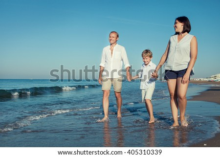 Happy family walk together on the sea surf line - stock photo