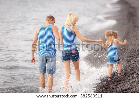 happy family walking along the beach at sunset. feet are in the water - stock photo