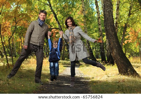 Happy family walking at the autumn park.