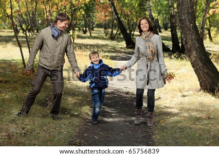Happy family walking at the autumn park. - stock photo