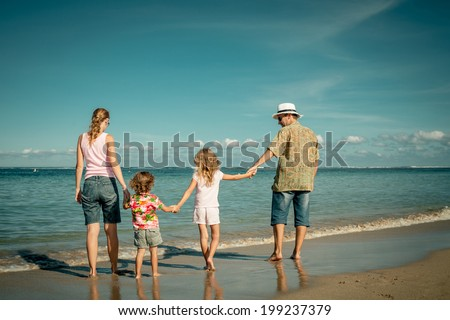 Happy family walking at the beach at the day time - stock photo