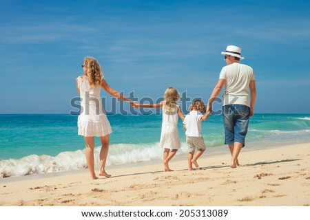 Happy family walking at the beach at the day time. Concept of friendly family.
