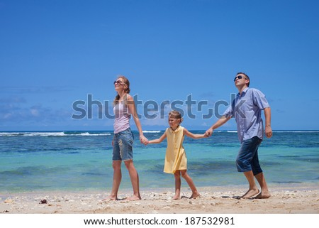 Happy family walking at the beach in the day time - stock photo