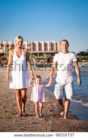 Happy family walking at the beach. Summer vacations
