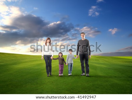 happy family walking in a grass field - stock photo