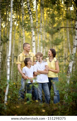 Happy family walking in the birch forest - stock photo