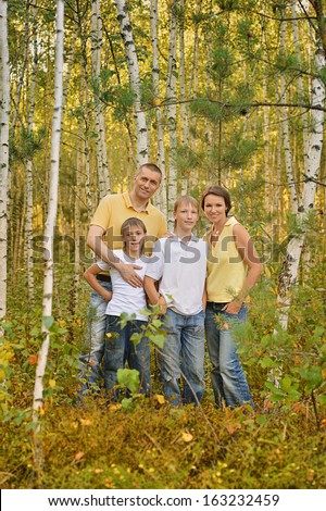 Happy family walking in the birch forest