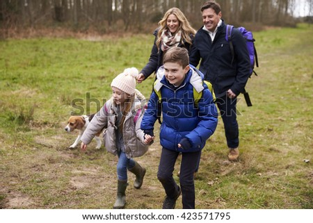 Happy family walking in the countryside with their dog - stock photo