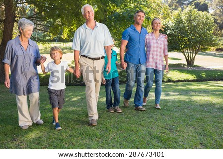 Happy family walking in the park on a sunny day - stock photo