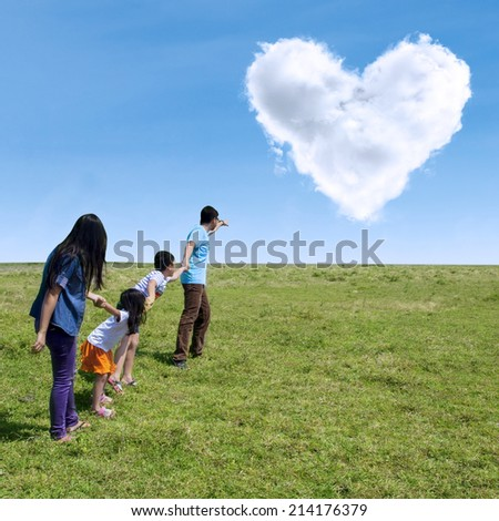 Happy family walking in the park with cloud of love in the sky - stock photo