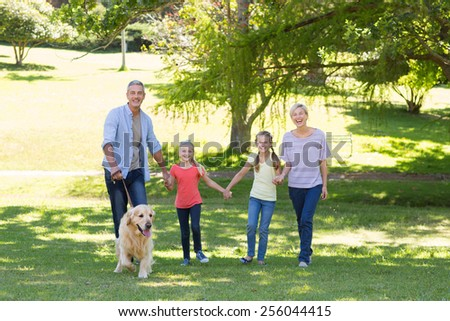Happy family walking in the park with their dog on a sunny day