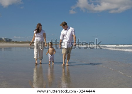 Happy family walking on a beach. Shore and blue sky in the background. - stock photo
